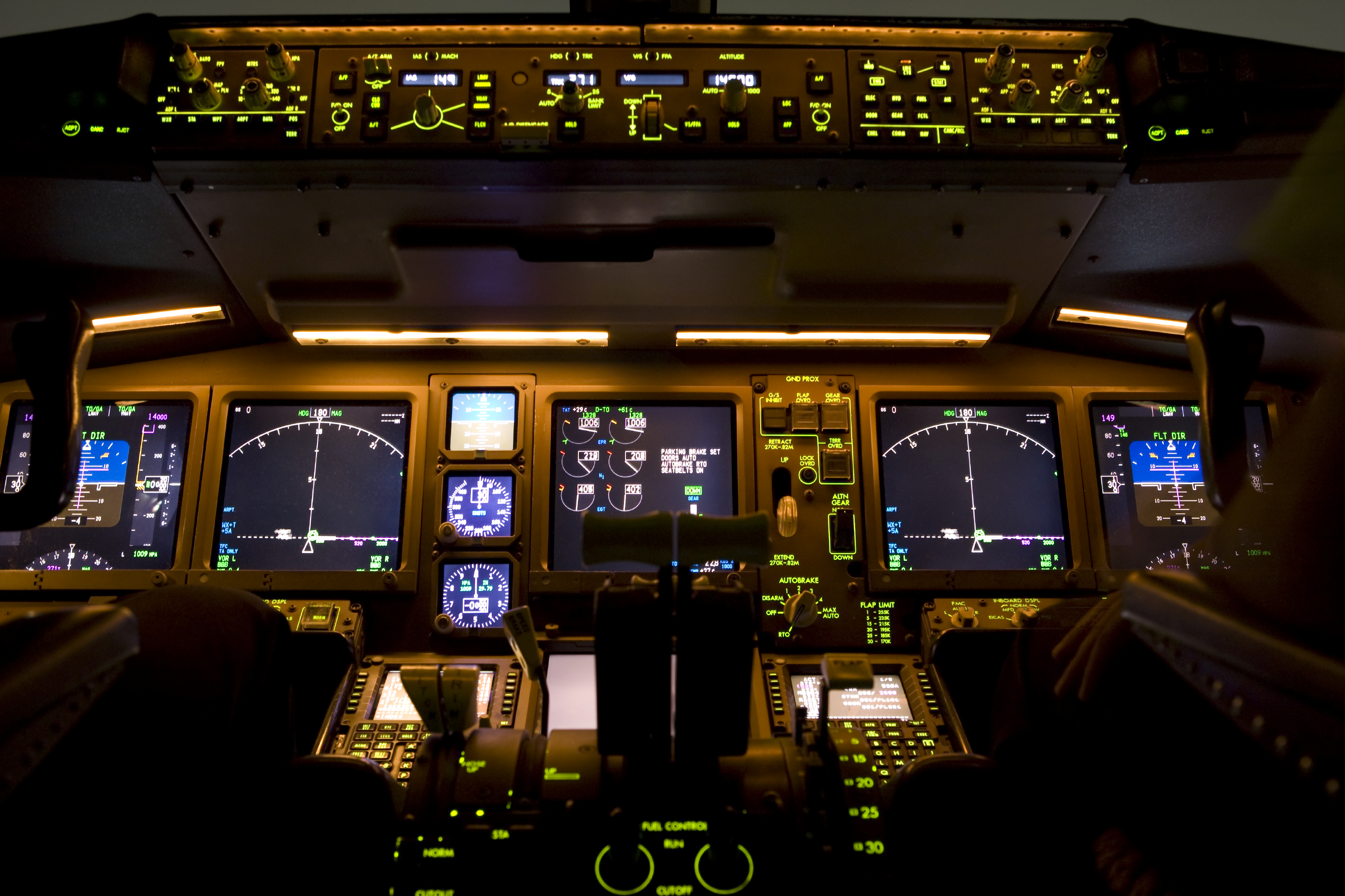 The muted lights of an airline cockpit at night.